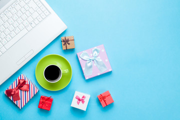 Cup of coffee with gift boxes and computer