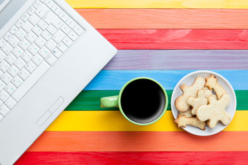 Cup of coffee with cookies and laptop