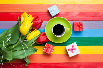 Cup of coffee with tulips and gifts