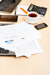 paper charts and modern office tools on table