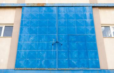Big blue closed metal gate of Industrial building