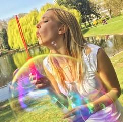Mädchen macht Seifenblasen im Park