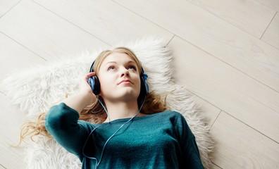 Beautiful blond woman listening to music through headphones