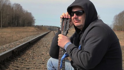 Lonely Man with guitar on the railway