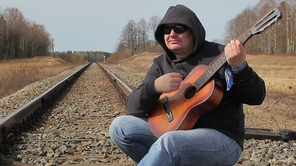Man playing guitar on the railway