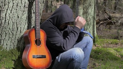Stressful Man with guitar in the forest