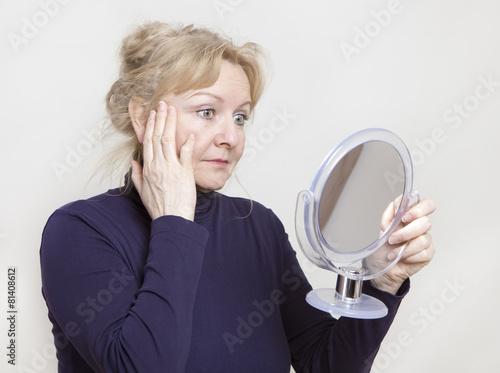 Leinwanddruck Bild Seniorin schaut in Spiegel
