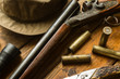 Hunting rifle, ammunition, a knife and a cap on the table - 81409482