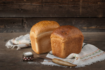 Two loaves of bread, knife, salt lying on a wooden surface