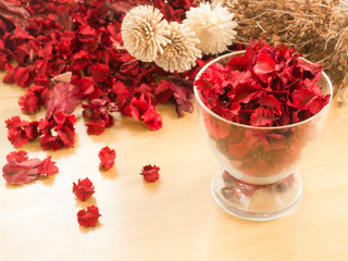 Red Dried flowers in glass on a wooden background