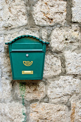 Green mailbox on stone wall