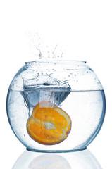 Orange falls under water with big splash