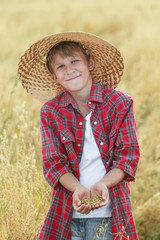 Smiling teenage farmer checking oat seeds in cupped palms