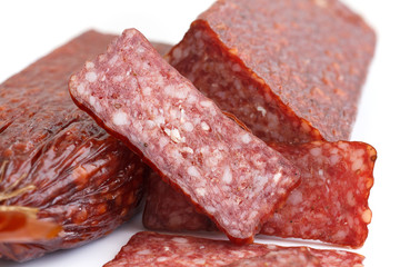 Premium salami, cut, sliced on white. Macro.