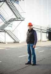 Confident engineer posing against warehouse