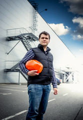 young architect posing with hardhat against industrial building