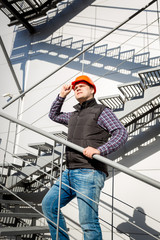 male worker in hardhat standing on steel staircase