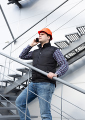 architect talking on phone while inspecting factory