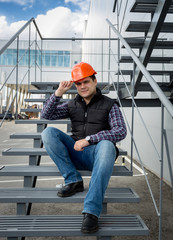architect wearing hard hat sitting on metal staircase at factory