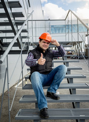 builder in helmet sitting on metal staircase and showing thumb u