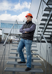 young architect in hard hat posing on metal staircase