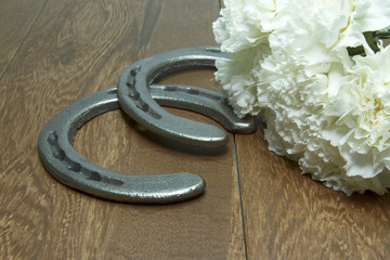 White Carnations for the Belmont Stakes with Horseshoes on Wood