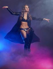 Fantastic female dancer in glow of purple smoke