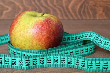 Apple and measuring tape on wooden background