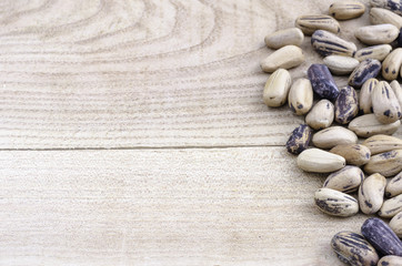 Pine nut with shell over wood, space text.