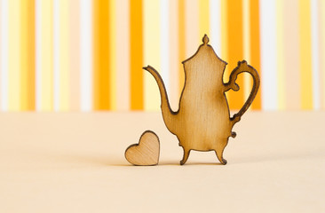 Wooden icon of teapot with little heart on orange striped backgr