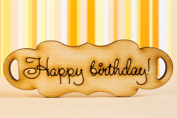 """Wooden plaque with the inscription """"Happy Birthday"""" on orange st"""