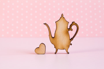 Wooden icon of teapot with little heart on pink background