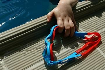 Child hand grabbing children swim goggles from edge of pool