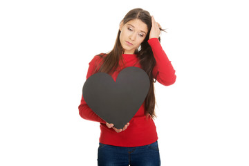 Worried woman with heart made from paper.