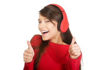 Woman with thumbs up listening to music.