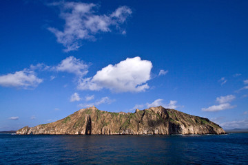 Scenic landscape of small volcanic island with blue skies on the
