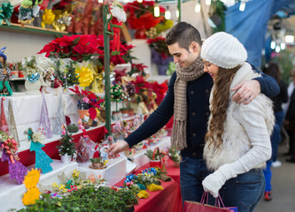 Couple buying Christmas flower at market