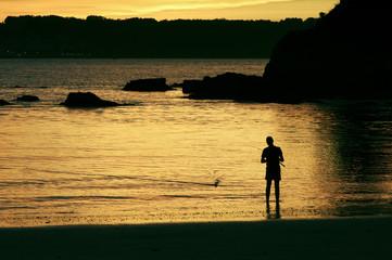 fisherman on the beach at dusk