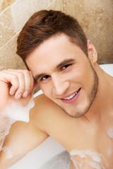 Handsome man taking a bath.
