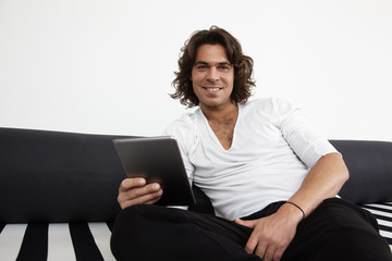 smiling man with a tablet on a sofa