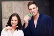 Couple in the bathroom brushing teeth.