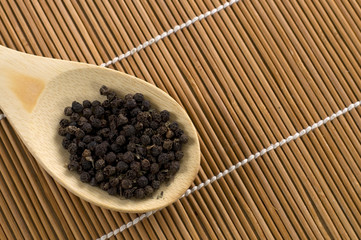 Black Pepper in a Wood Spoon on Bamboo