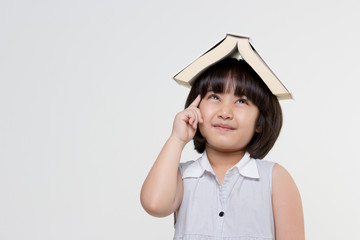 Portrait of little Asian child put a book on top