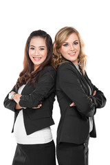 Two young businesswoman smiling while leaning againts each other