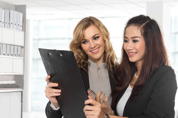 two young businesswoman wtih a clipboard