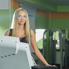 Gym. Attractive blonde exercising on treadmill