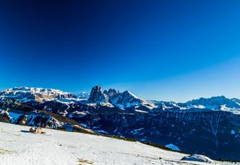 panorama of the Dolomites with chalet,  snow-capped peaks and co