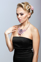 Blonde woman in black dress and necklace