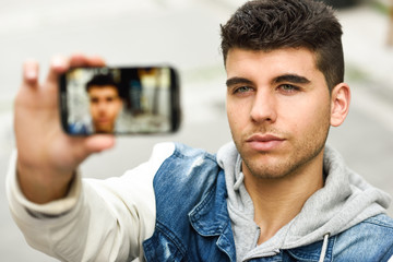 Young man selfie in urban background with a smartphone