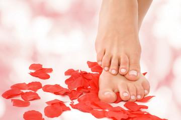 schöne Füße stehen in Rosenblättern